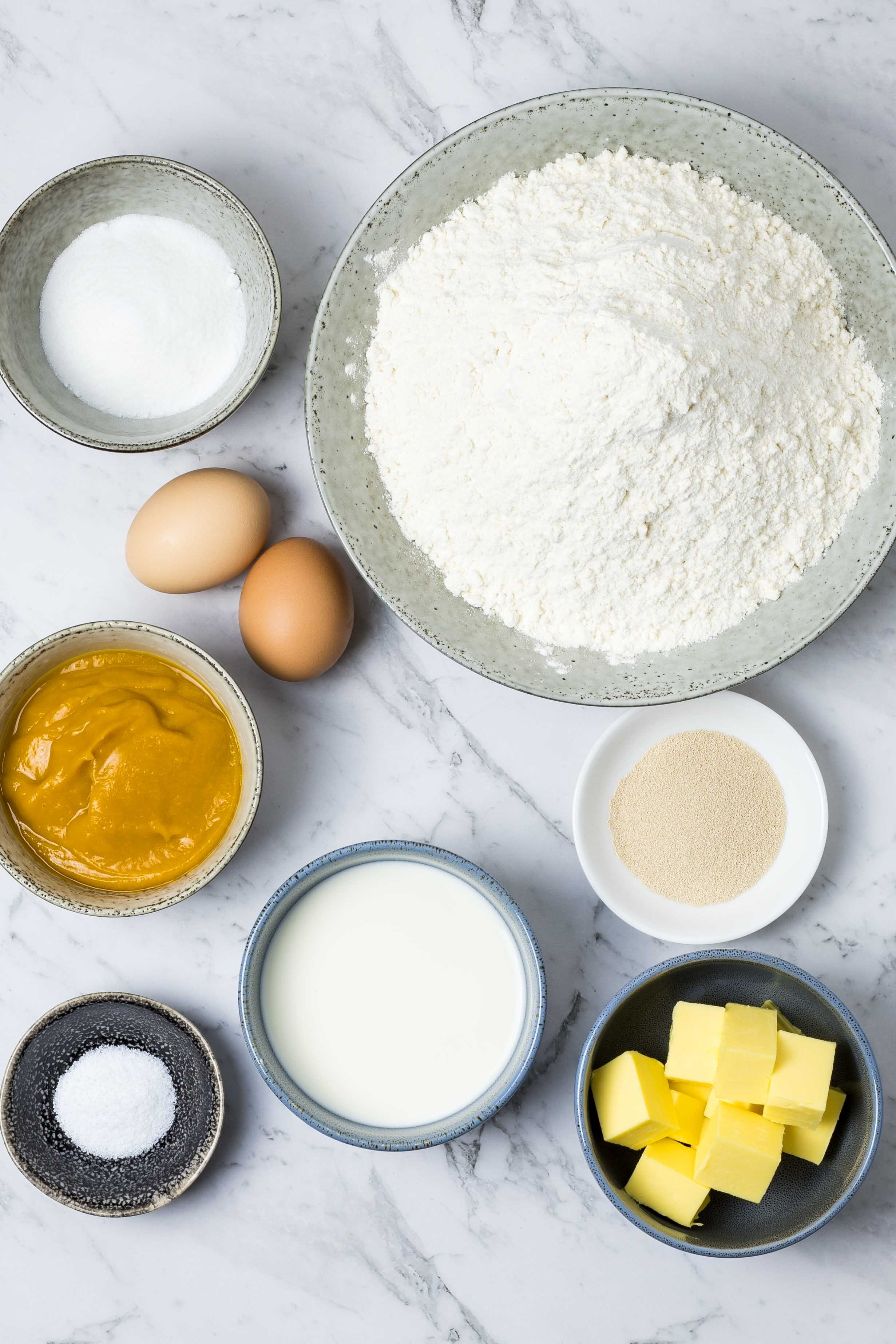 Ingredients for pumpkin dinner rolls: flour, yeast, butter, milk, salt, pumpkin puree, eggs and sugar