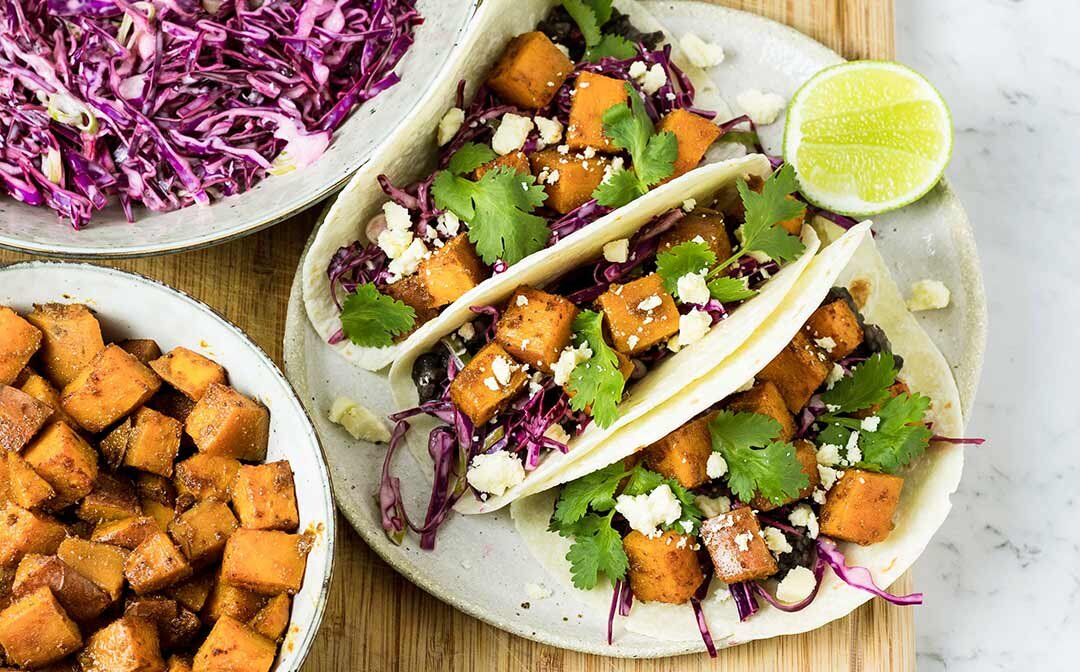 Three roasted sweet potato tacos with black beans, cabbage slaw, coriander and feta cheese, with a wedge of lime for serving