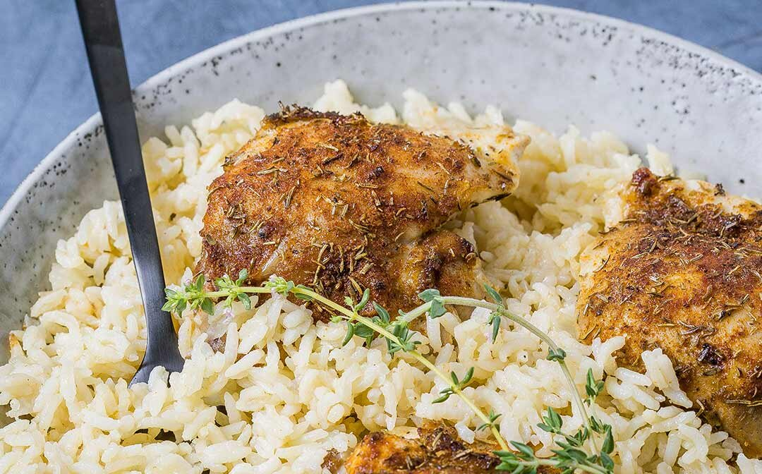Steam oven baked chicken and rice, served in a stoneware bowl with fresh thyme garnish