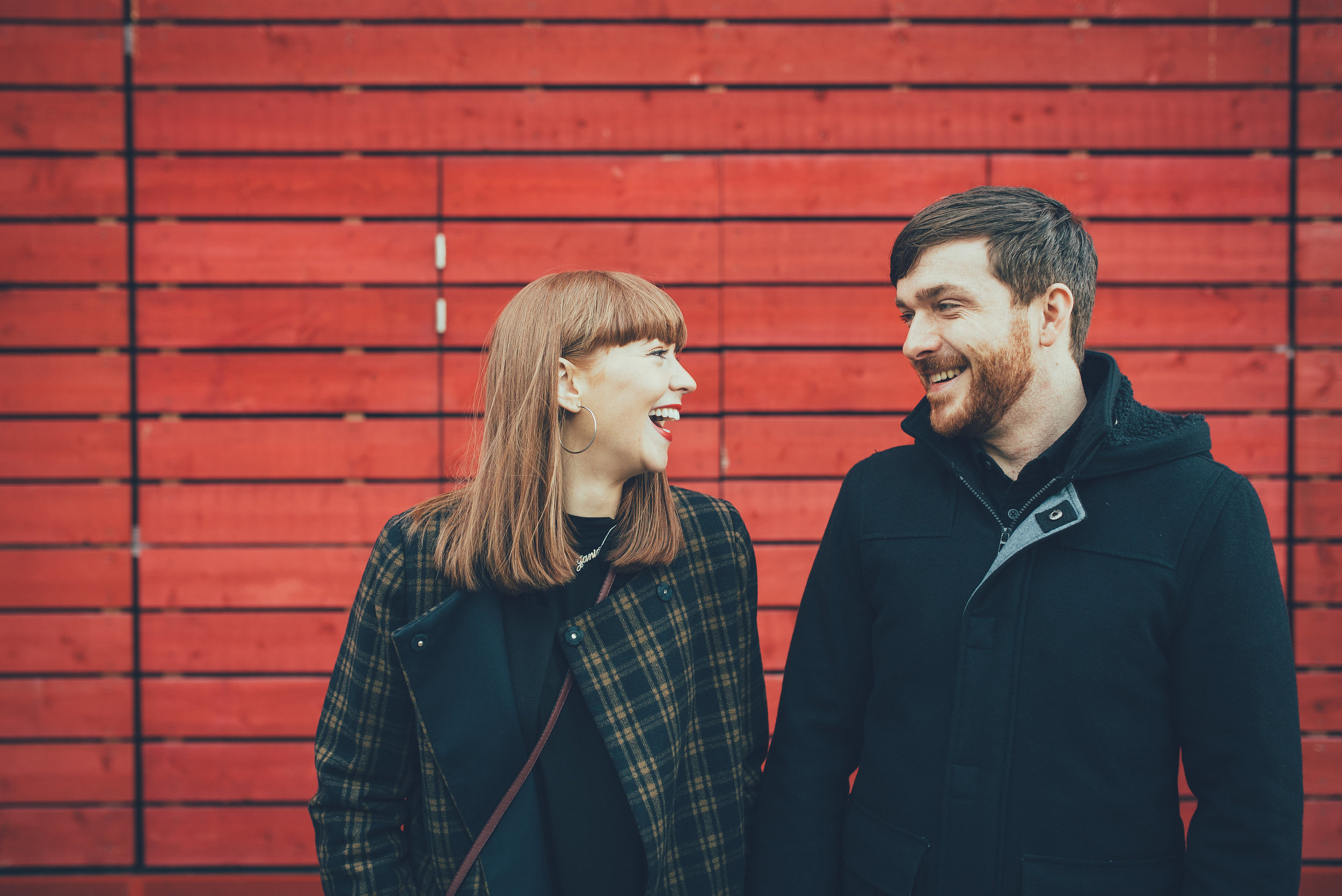 Couple laughing in front of red wall at the National Theatre London