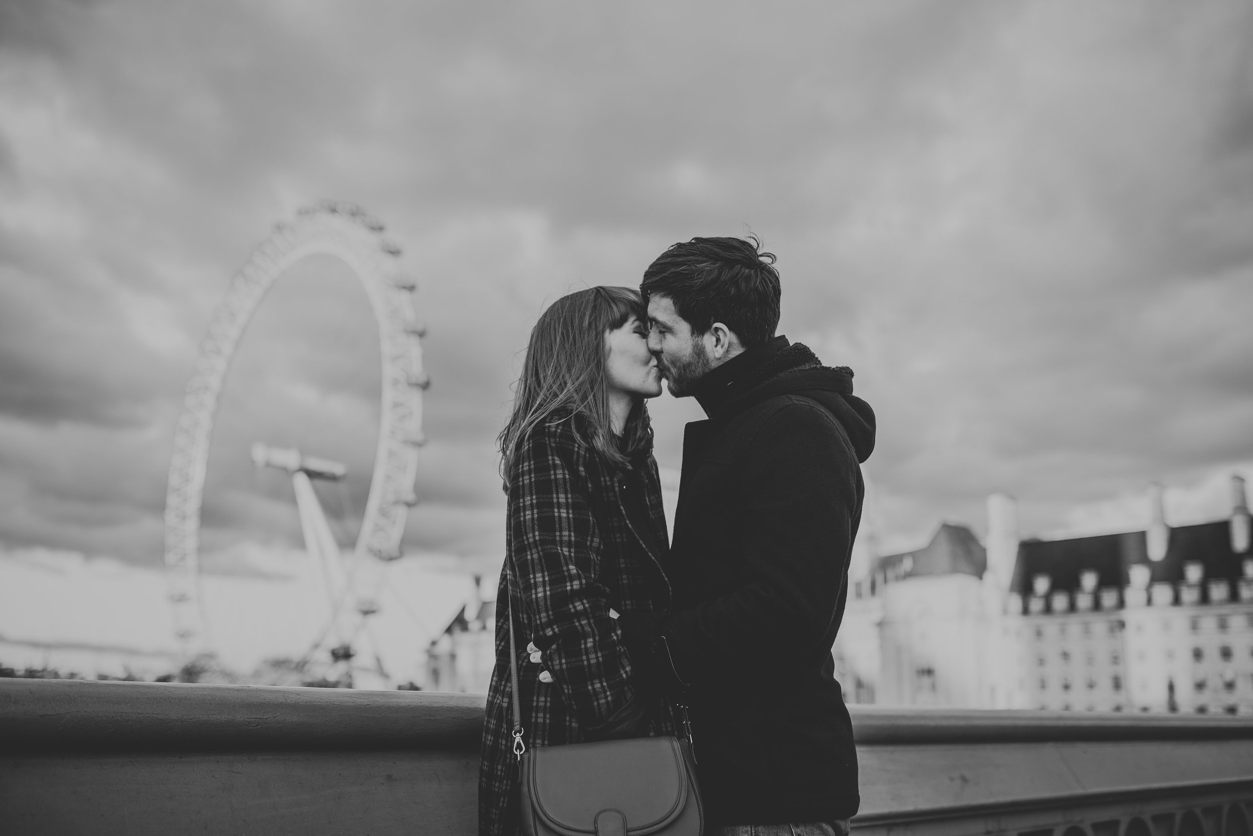 Engaged couple in love kissing in front of London Eye