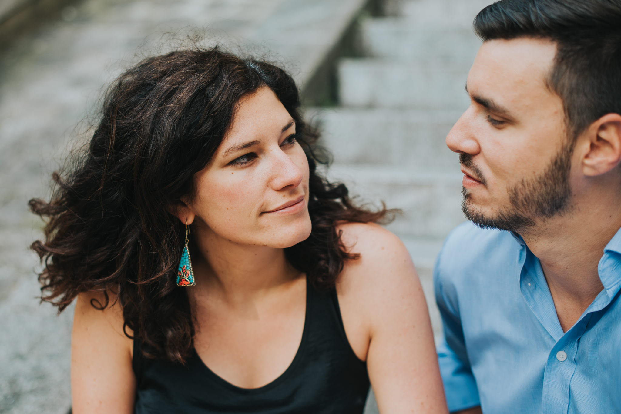 Close up of woman looking at man that she loves, sitting on steps
