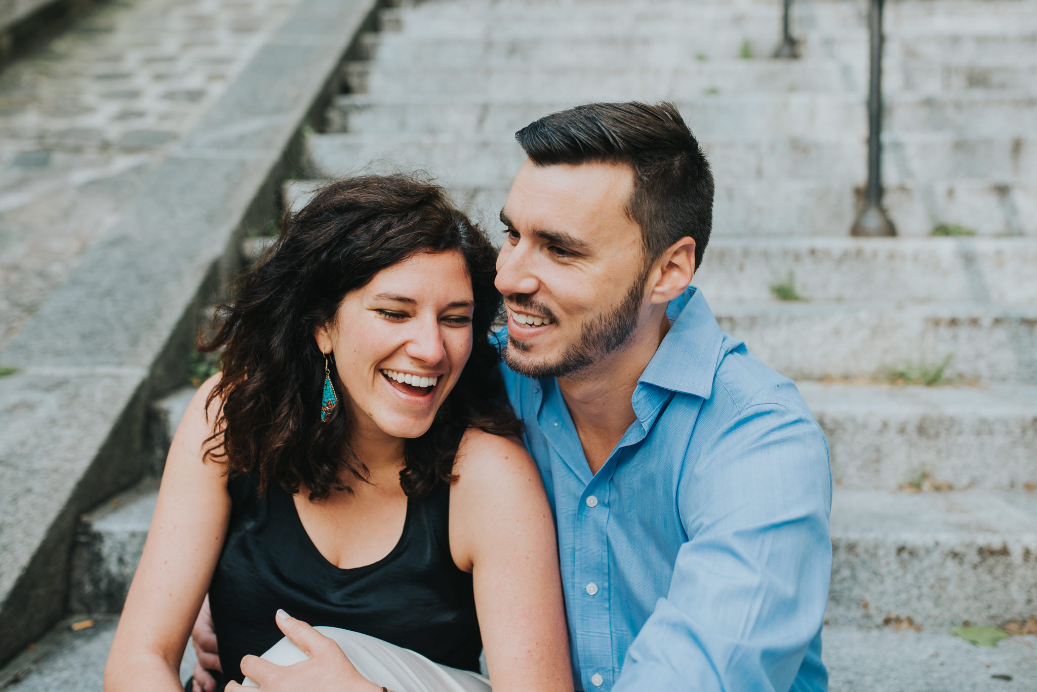 Close up of man and woman laughing on steps in Paris