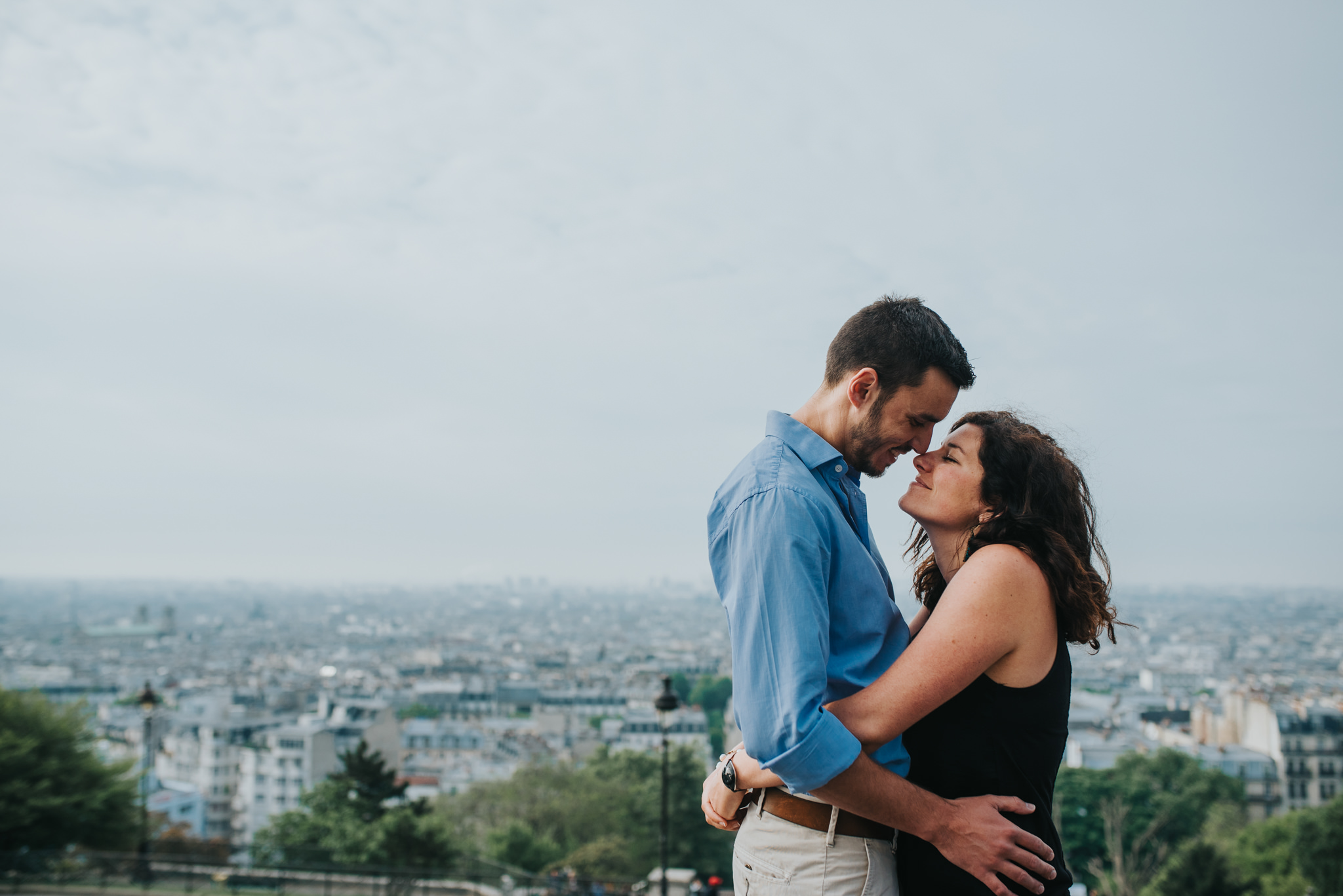 Engagement shoot couple in love embracing with Paris skyline in the background