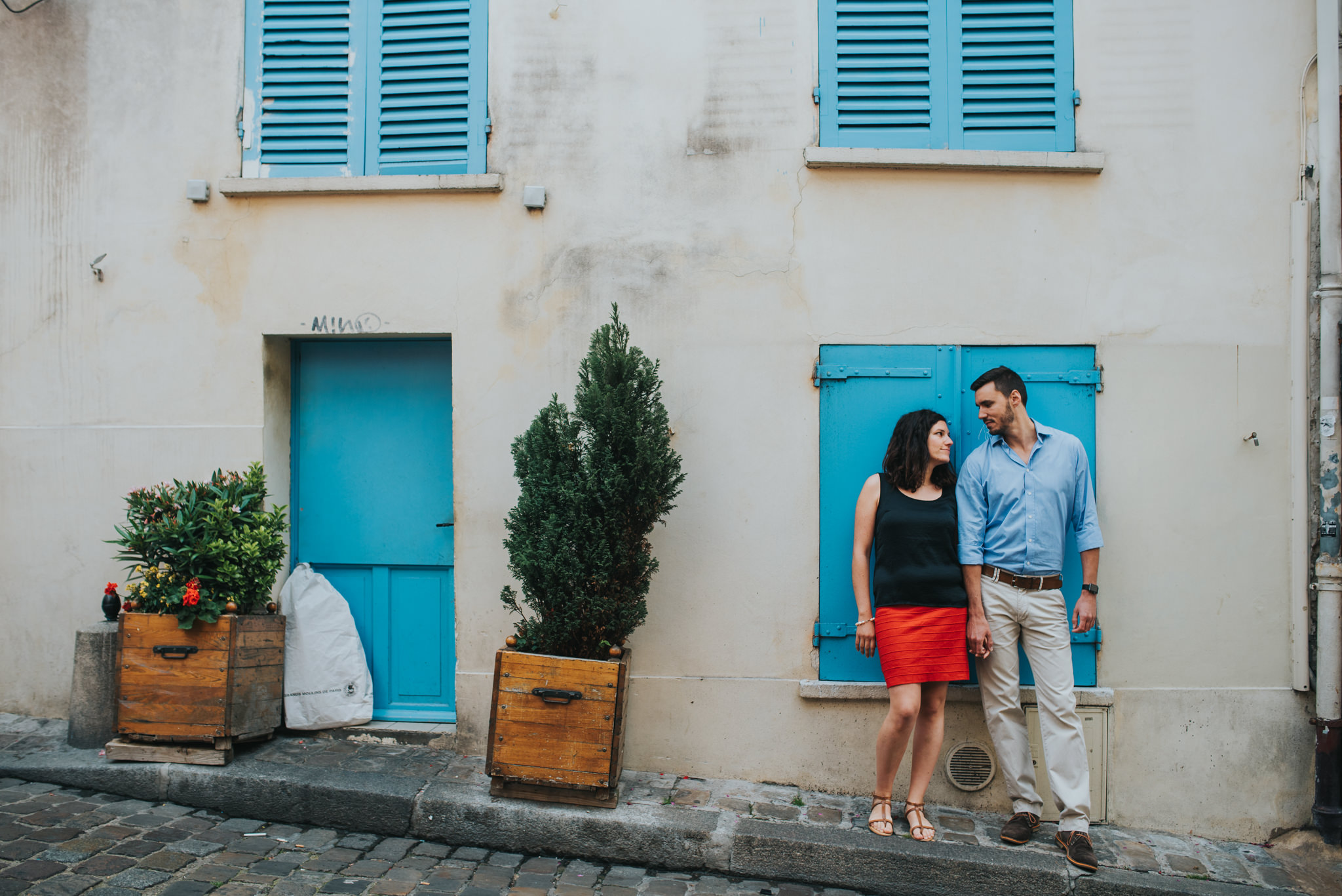 Couple in love holding hands on Montmartre street with traditional building in the background