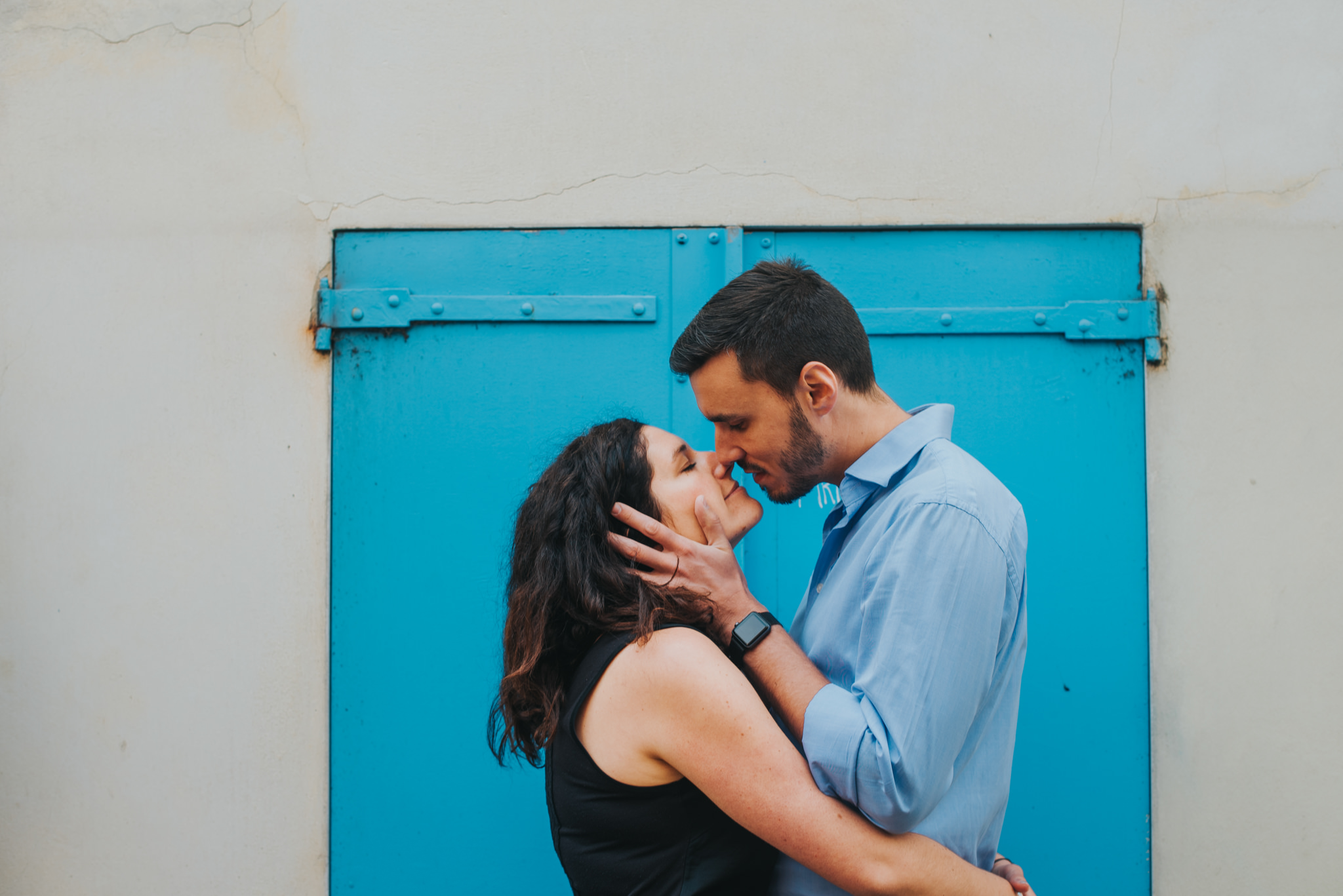 Couple in love kissing on Montmartre street with blue shutters in background