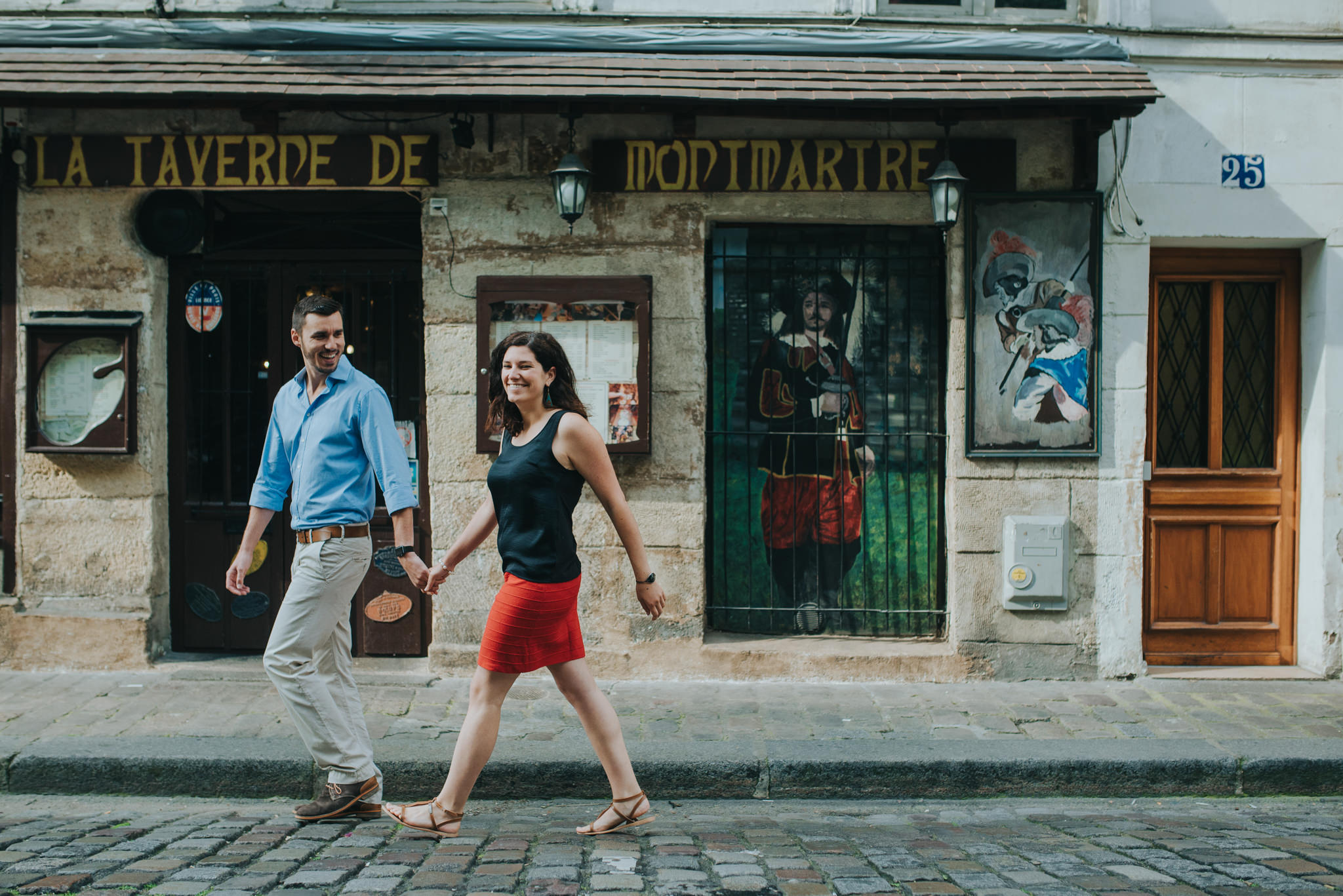 Paris pre-wedding photoshoot couple in love walking by red cafe in Montmartre