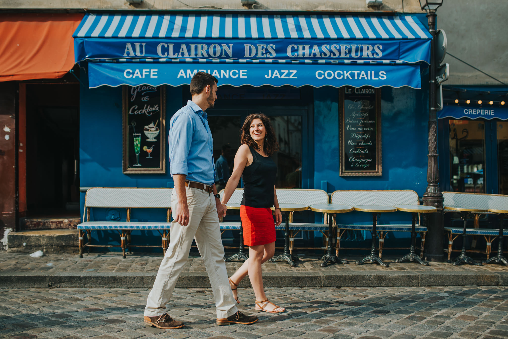 Paris pre-wedding shoot: Man and woman in love walking by one of the cafes in Montmartre.