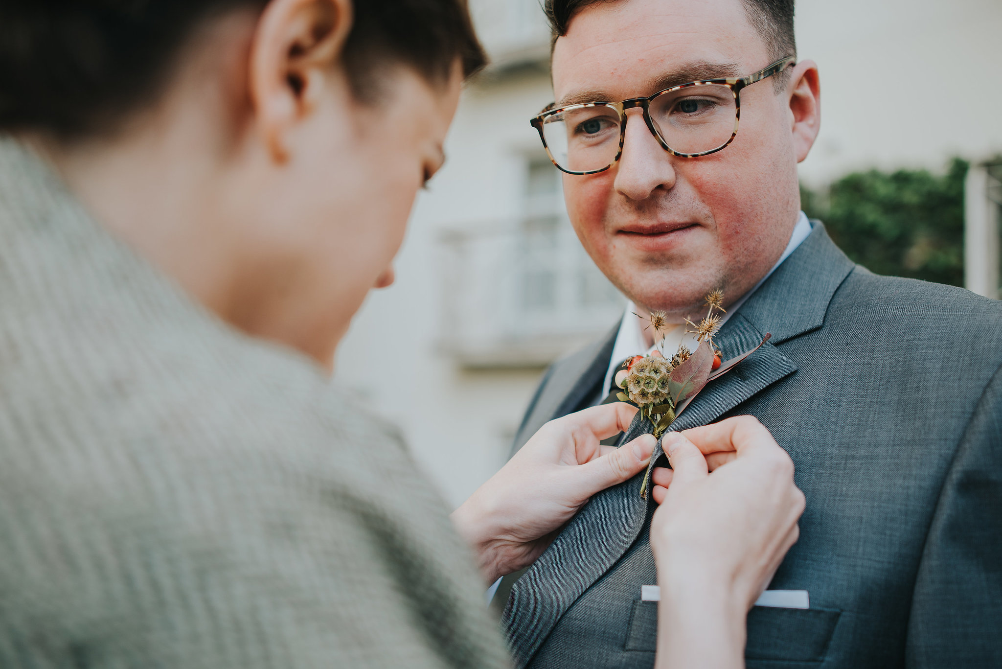 Bride fixing her groom's buttonhole on their wedding day