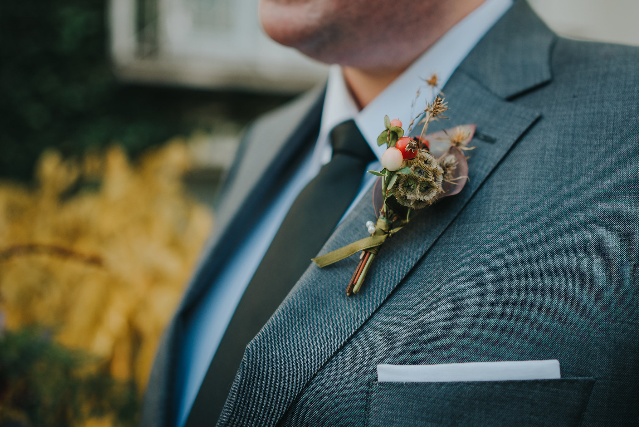 Close up of groom's button hole on wedding day