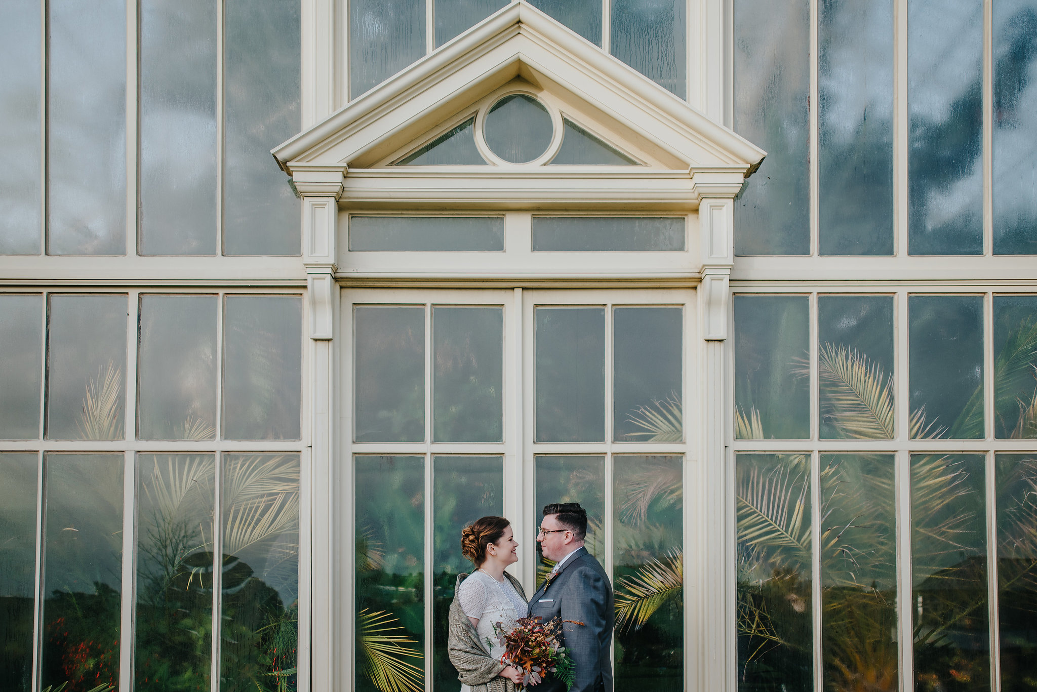 wedding photography of bride and groom standing in front of greenhouse at Botanic Gardens Dublin on their wedding day