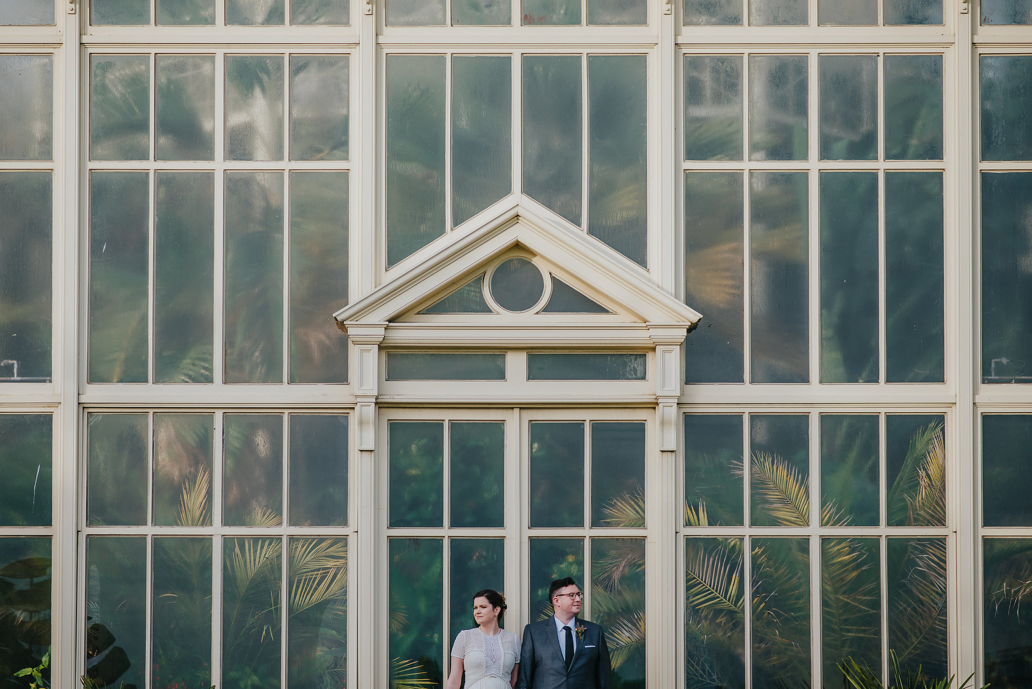 Alternative wedding photography of bride and groom in front of greenhouse at Botanic Gardens Dublin