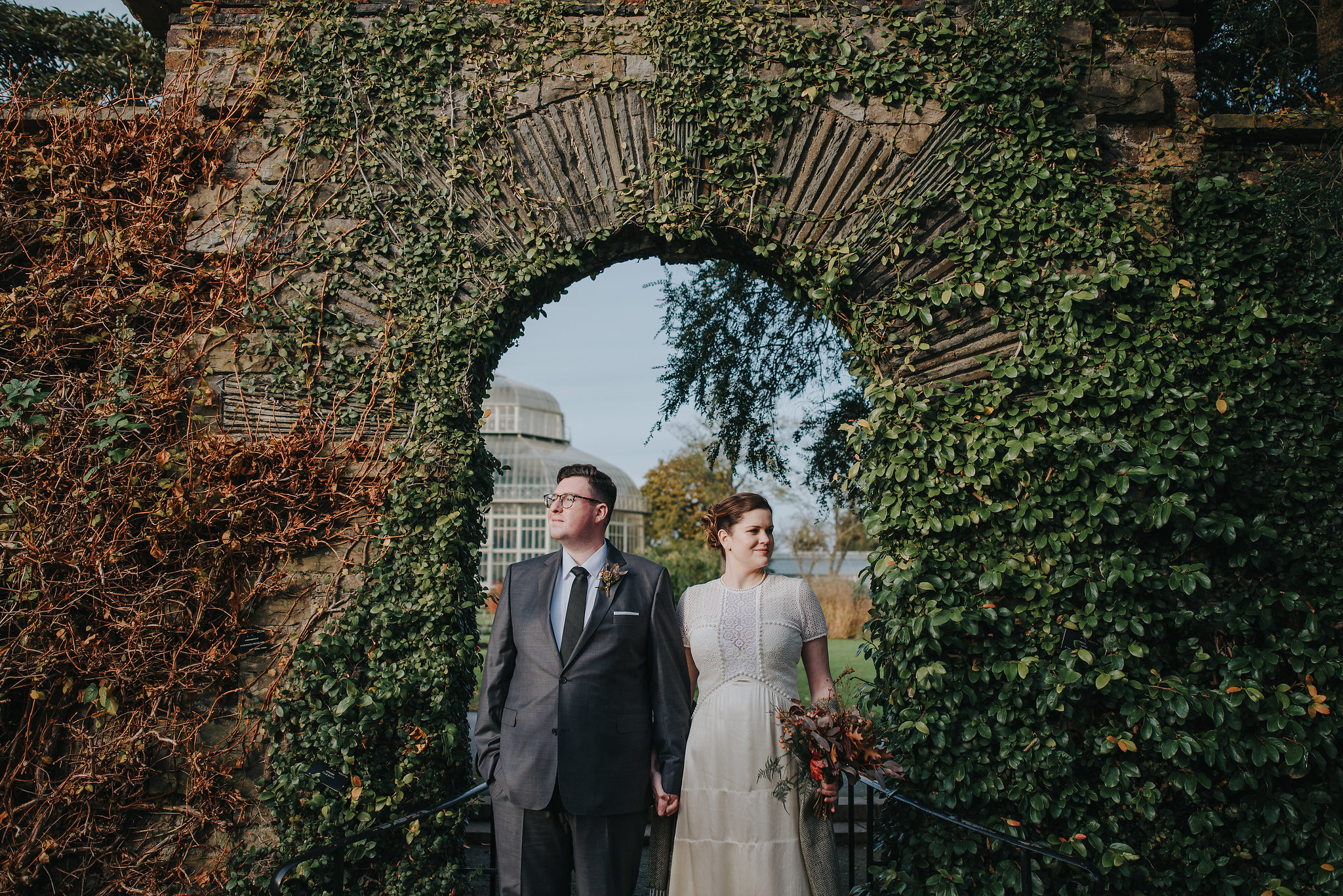 Bride and groom standing in archway at Botanic Gardens