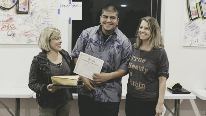 Kathyrn Stellmacher and Lauren Segal present a Certificate of Completion to Project Kinship member Christian Padilla.