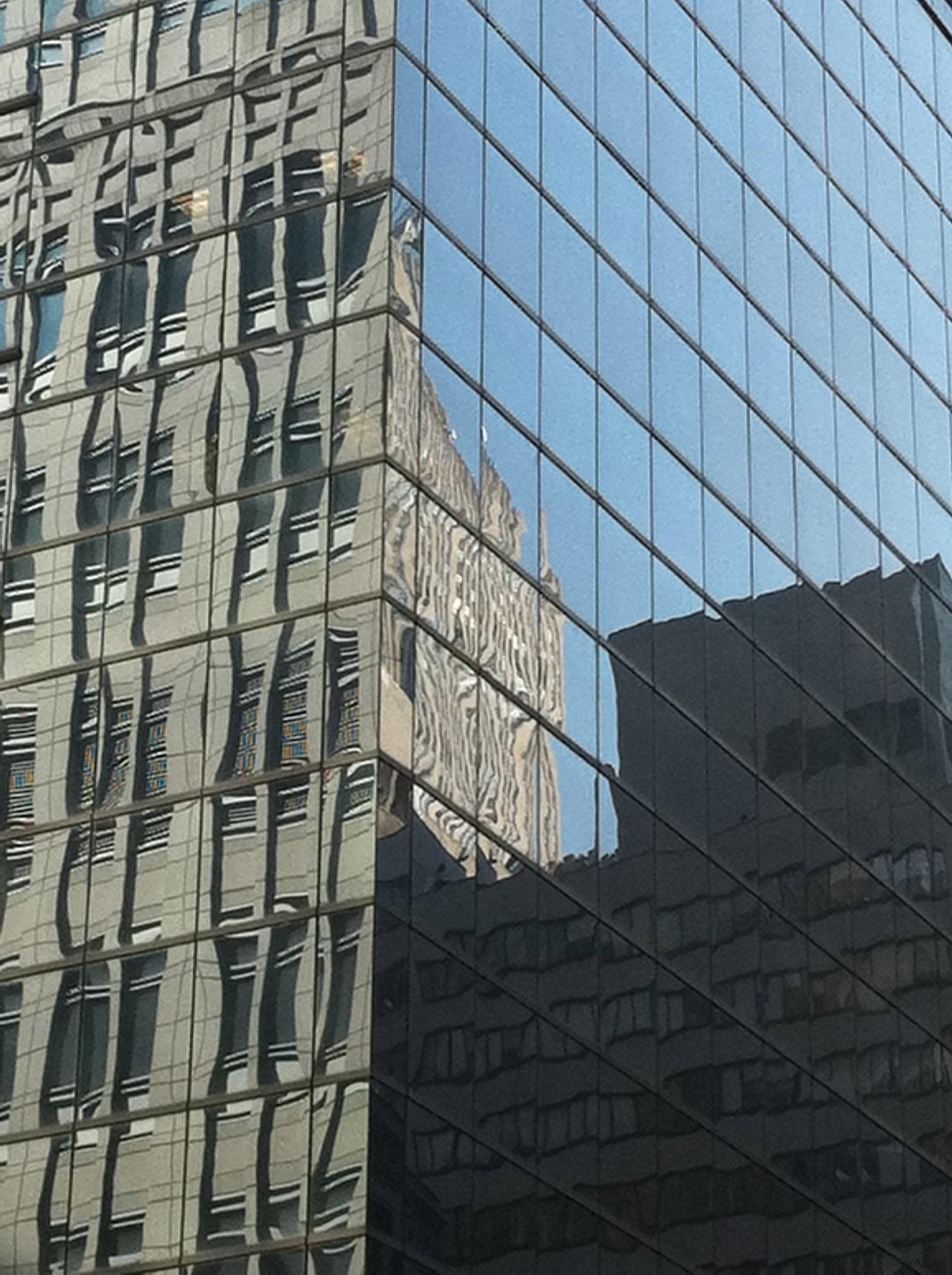 a building reflects on the glass building's exterior