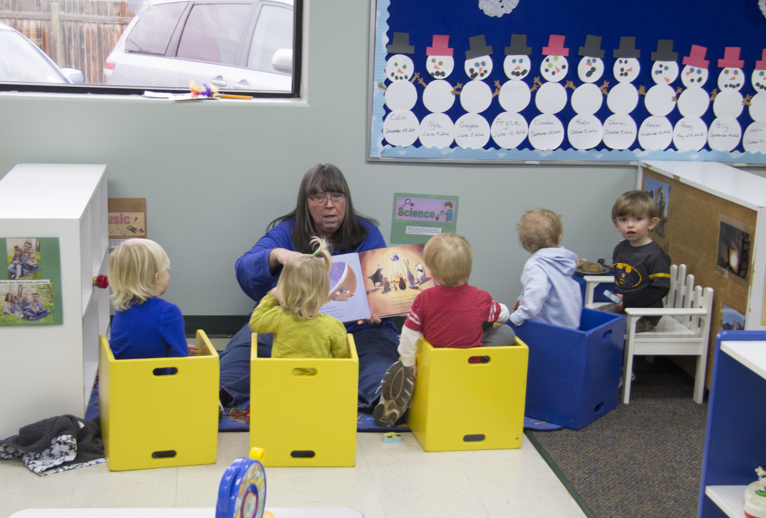 Wobbler/toddler teacher cindy reads to students in A tlc toddler room.