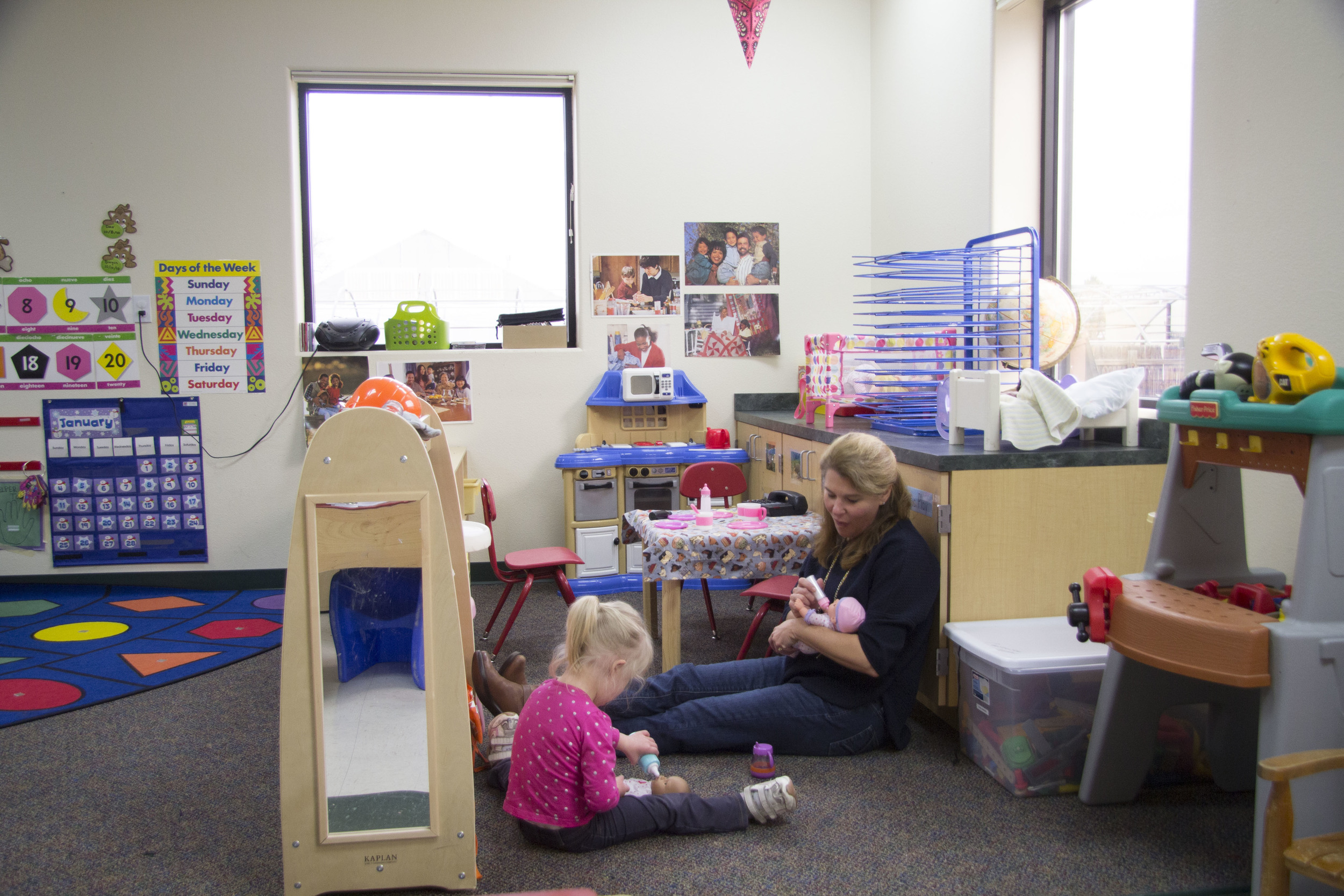 A teacher plays one on one with a child in a tlc preschool classroom