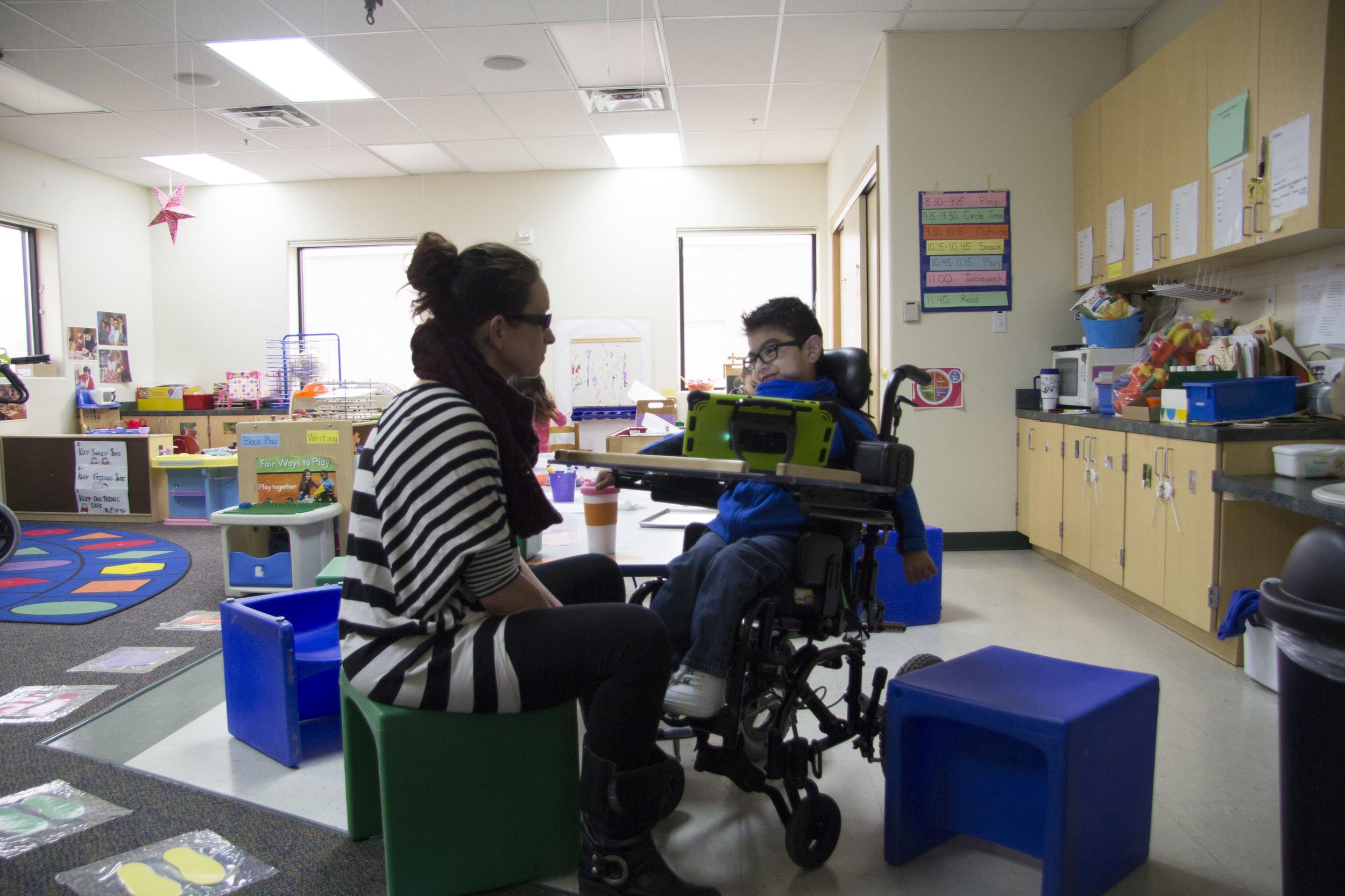 a tlc teacher works with a tlc preschool student using a communication device
