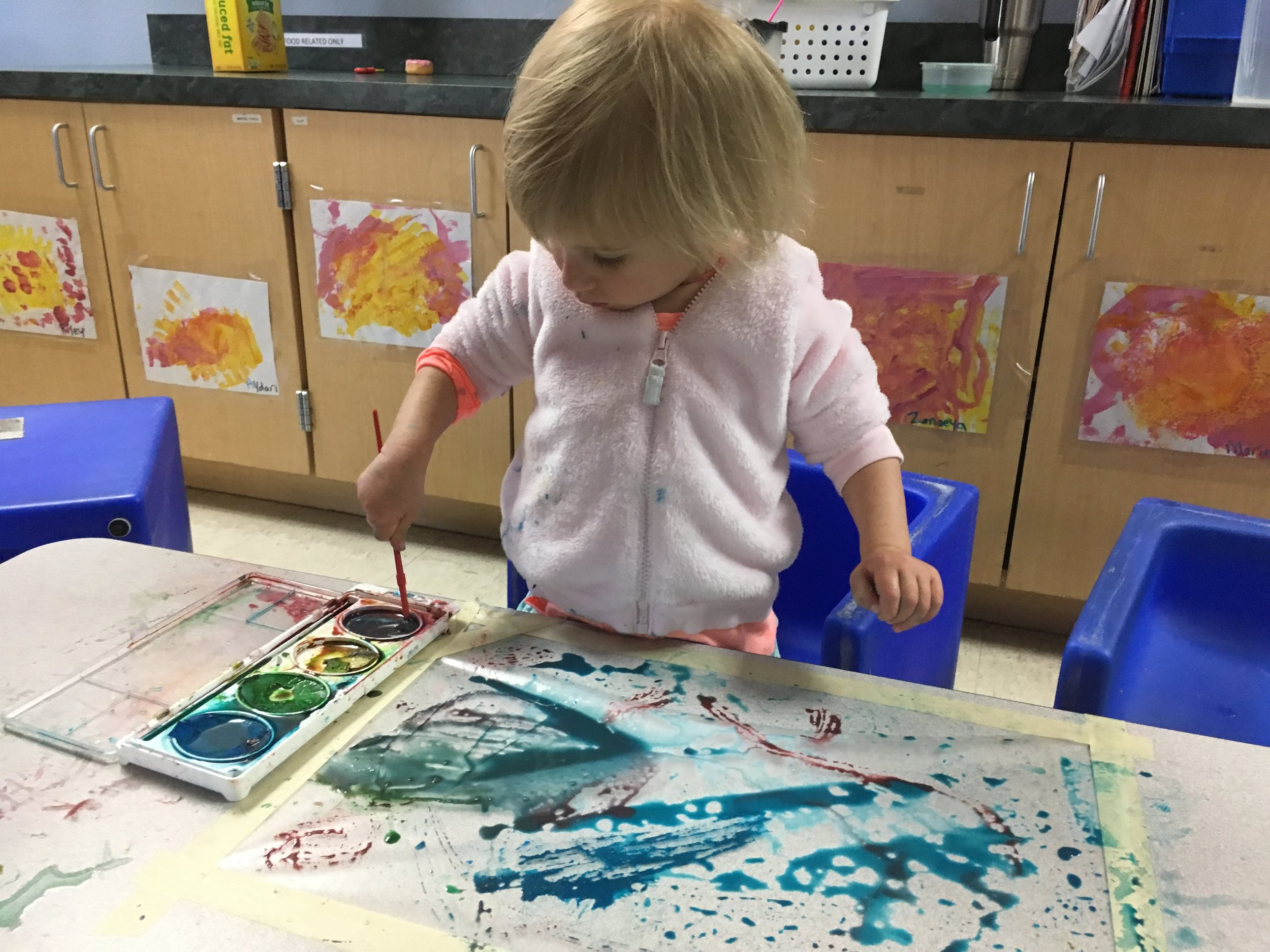 Riley enjoys painting contact paper with watercolors for a fun sensory activity in her toddler classroom.