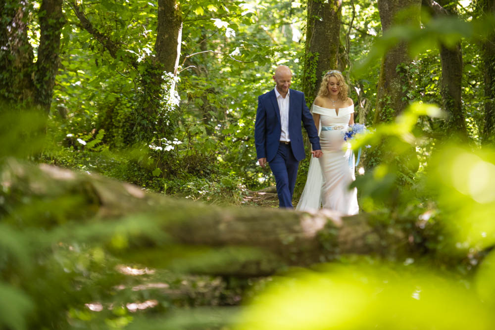 bride and groom walk in woods.jpg