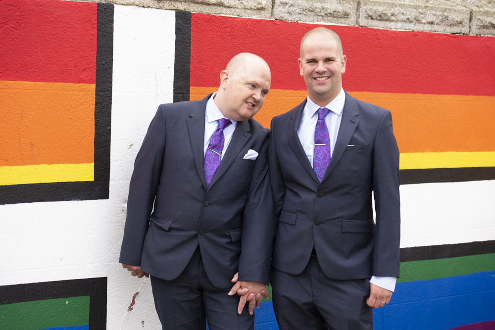 Grooms in front of pride wall