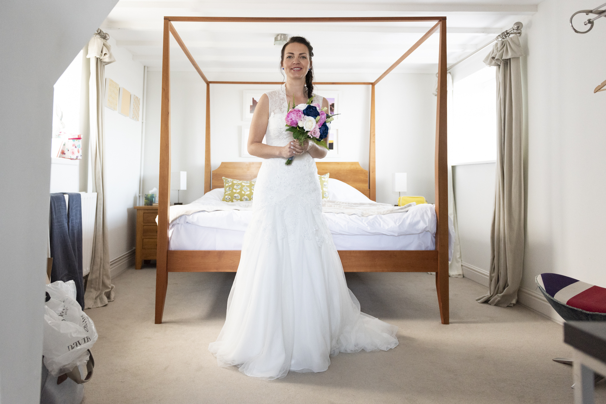 Bride in front of four poster bed