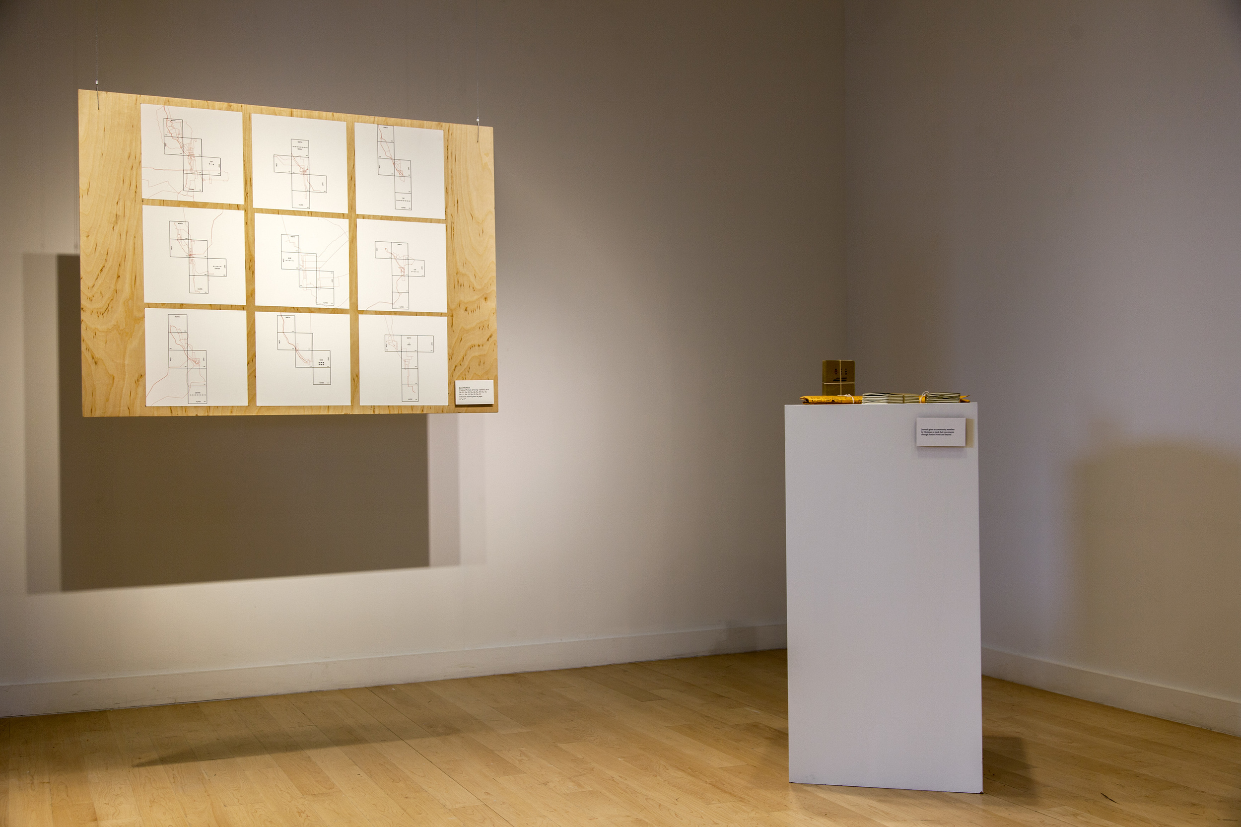 An installation shot of final artwork by Jason Hoylman. Maps representing the paths of his neighbors, and their journals on a pedestal.
