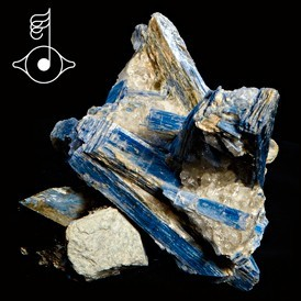 """Kyanite crystals,  possibly from Switzerland, are the """"cover"""" image for the digital download of Björk's """"Cosmogeny"""" remixes by Matthew Herbert. The title refers to the origin or evolution of the universe. Björk also holds the specimen in an image for the Serban Ghenea mix of the same song."""