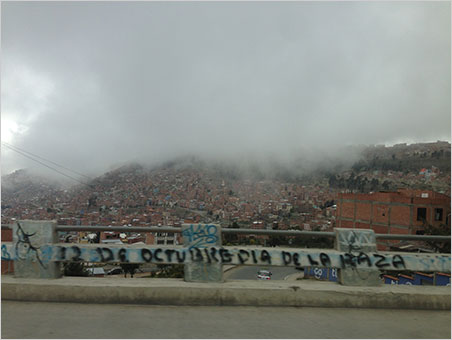 """The fog of war. This guardrail graffito pays homage to the uprising of the people (la raza) that began October 12, 2003, leading to the resignation of President Gonzalo """"Goni"""" Sánchez de Lozada. Two years later, one of the protesters, Evo Morales, would be elected President. (Photo: Will Larson)"""