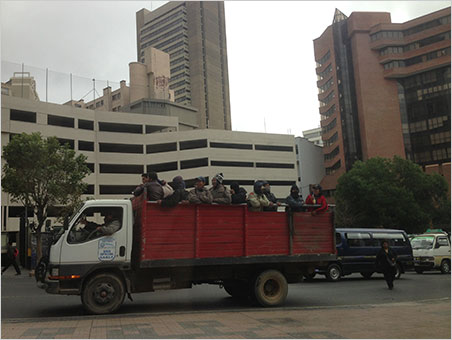 Truckin'. Landscape workers are transported through the concrete jungle of La Paz, a metropolis of about 2.5 million people. The worker in the middle wears a traditional Andeanchullohat that could have been knit from the wool of the llama Will ate at lunch. (Photo: Will Larson)