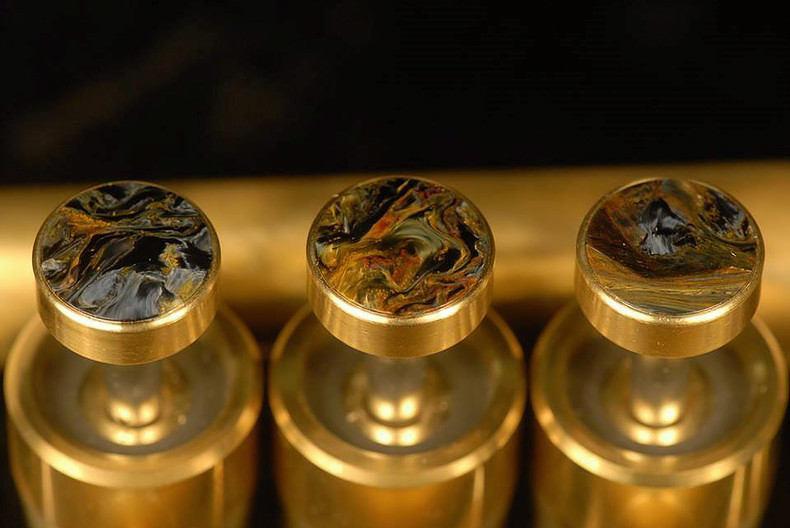 Brass instrument fingerbuttons inlaid with pietersite. (Photo courtesy David G. Monette Corp.)