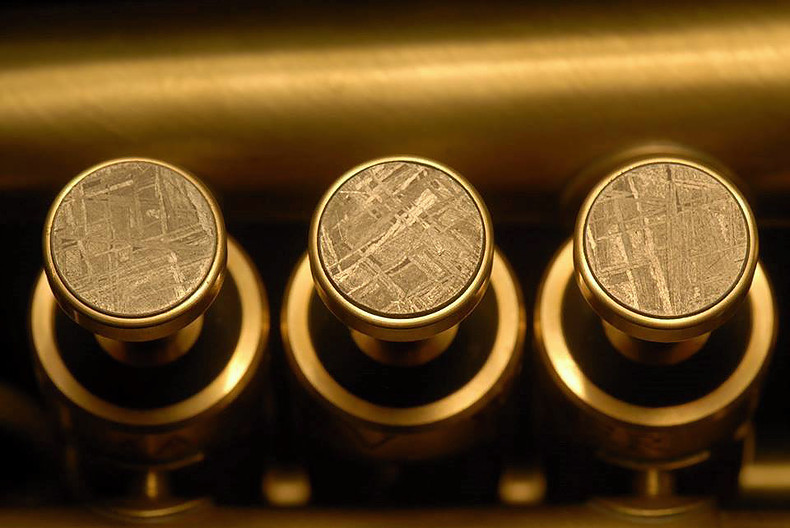 Brass instrument fingerbuttons inlaid with meteorite material. See also this  four-minute fingerbutton slideshow . (Photo courtesy David G. Monette Corp.)