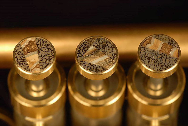 Brass instrument fingerbuttons inlaid with dinosaur bone and wooly mammoth tooth. Matching cufflinks would be classy. (Photo courtesy David G. Monette Corp.)