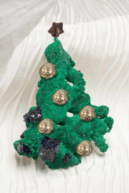 ¡Felices fiestas!  Malachite with azurite from the Milpillas Mine in Sonora, Mexico, 12 x 9.5 x 4 cm, topped with a 4.5 x 4 x 3-cm 5-star spinel from Burma, adorned with pyrite balls from China. (Photo: Mia Dixon)