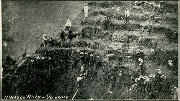 "Fig. 12.—Photograph showing ""peons"" working on a bank, breaking down the emerald formation with long, iron crowbars."