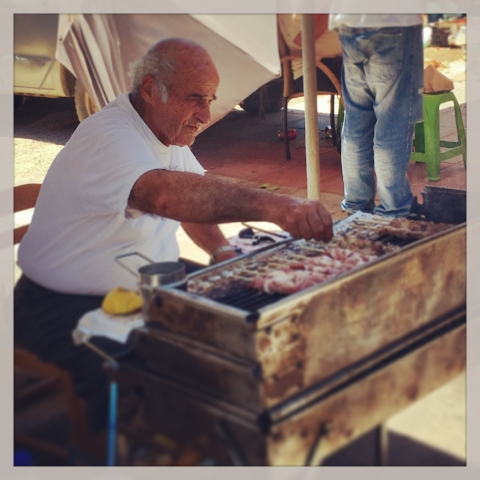 Vendor preparing 1-euro souvlaki sticks (pork and chicken)