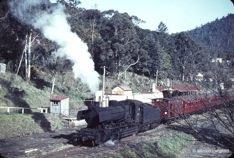 A J class steam engine at Warburton station in 1964, a year before the railway line closed. The scene was largely unchanged from 30 years earlier. Photo  © Weston Langford .