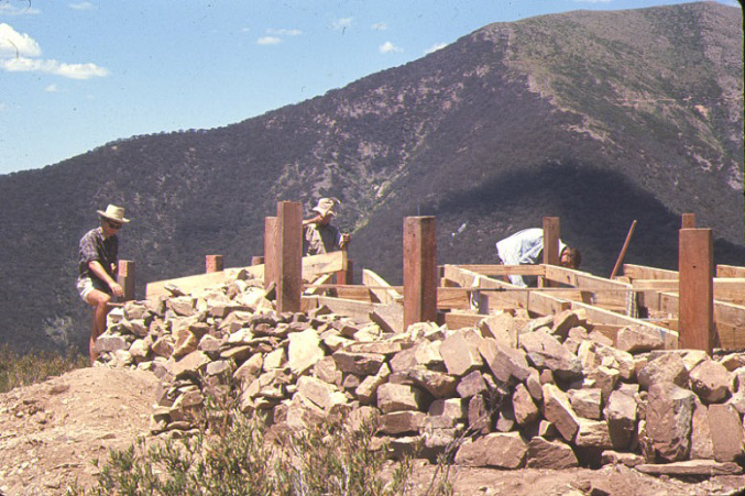 More progress – bearers, joists all strapped together. The track around the face of Feathertop can be seen above the right hand post – midway between the top of the post and the summit. The track was a natural cattle pad when cattle were permitted to graze up in the high country.