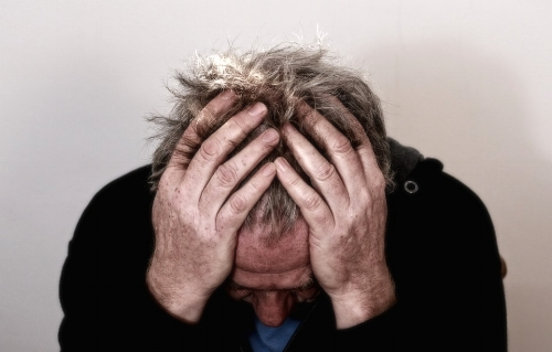 Photo of man with his head down in his hands