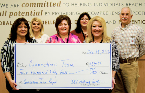 Photo of employees and check presentation.