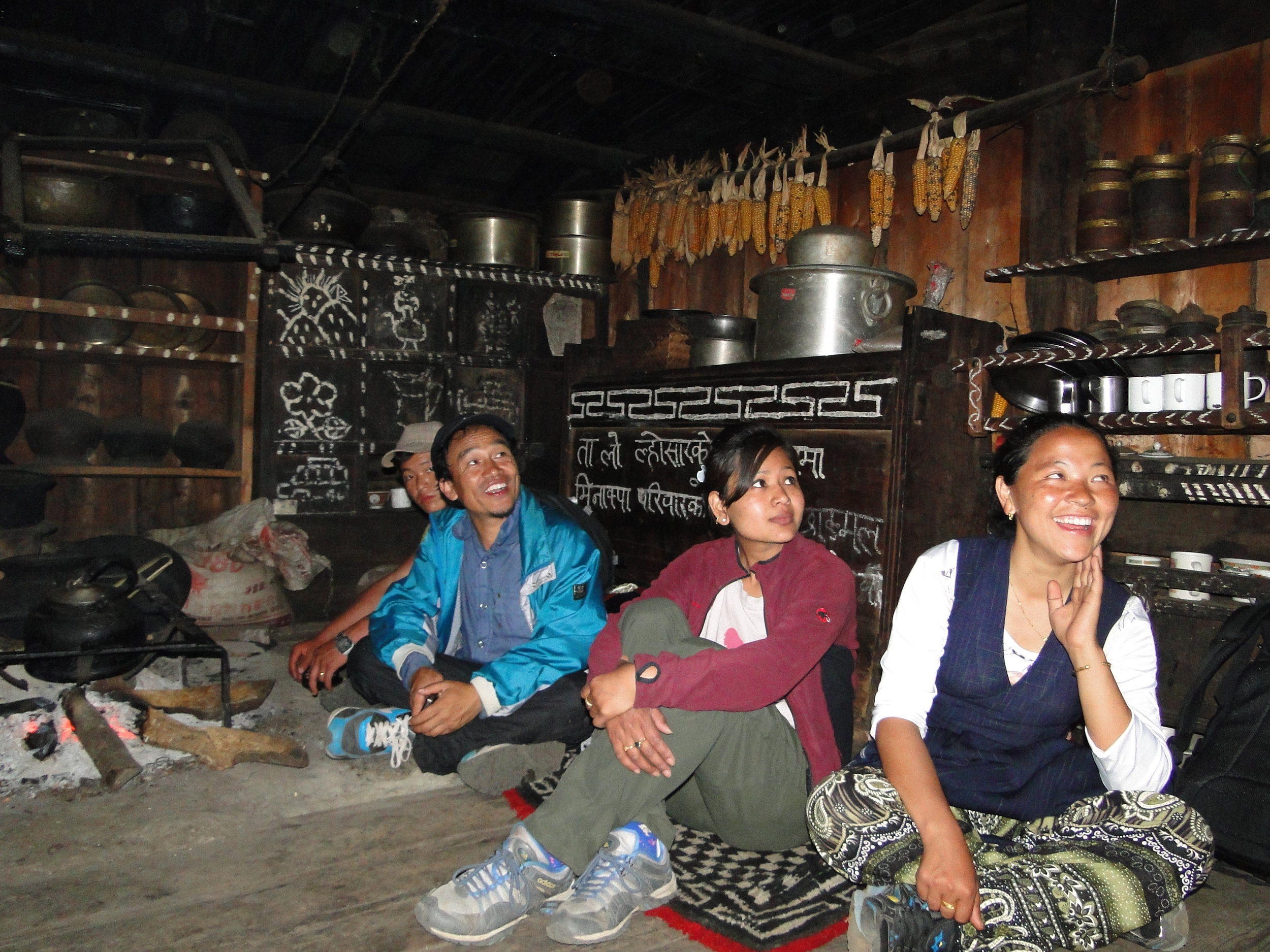 Chepuwa, Sankhuwasabha, 2016: A family sit round a traditional open hearth. Such fires result in high levels of smoke indoors, the roof is black is soot. Wood also burns quickly on an open fire, this means large quantities of wood need to be harvested, collected and stored. An environmentally damaging and time consuming process.