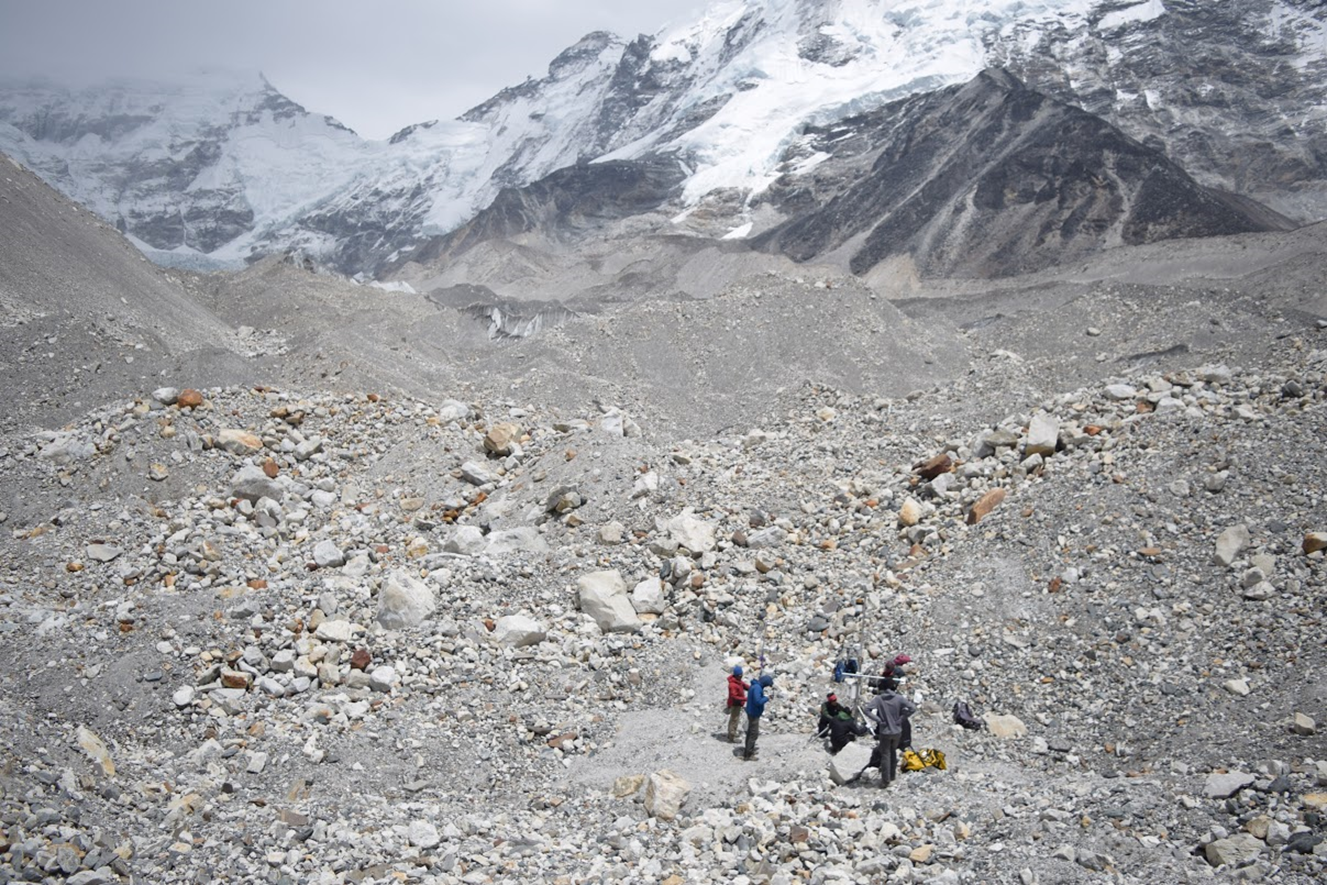 Figure 2 . The debris on this portion of Imja-Lhotse Shar Glacier commonly exceeded one metre. Here, an automatic weather station is being installed during a field expedition in April 2017 to better understand debris-covered glacier melt (credit: Chilton Tippin).