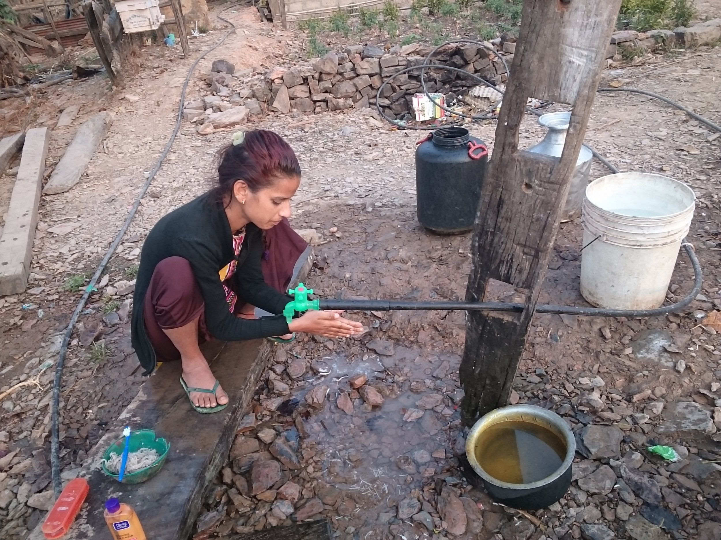 Lady uses new tap in Durlunga Baseni, Deurali to wash. TGT's projects are enabling improvements in health and hygiene.