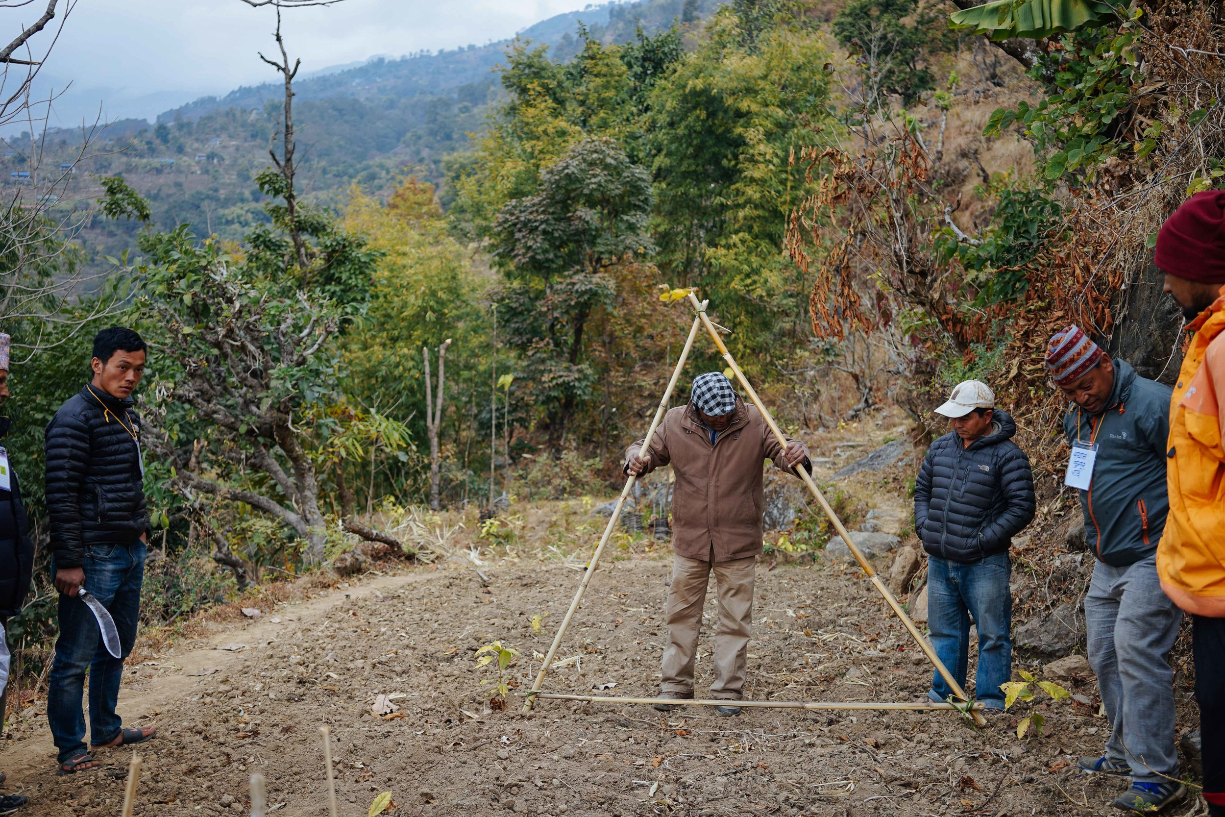 TGT funds training workshops where farmers are taught how to plant, grow, pick and process their coffee. When planting, the trees need to be an exact distance apart as coffee expert Bhola Shrestha from HELVETAS demonstrates here.