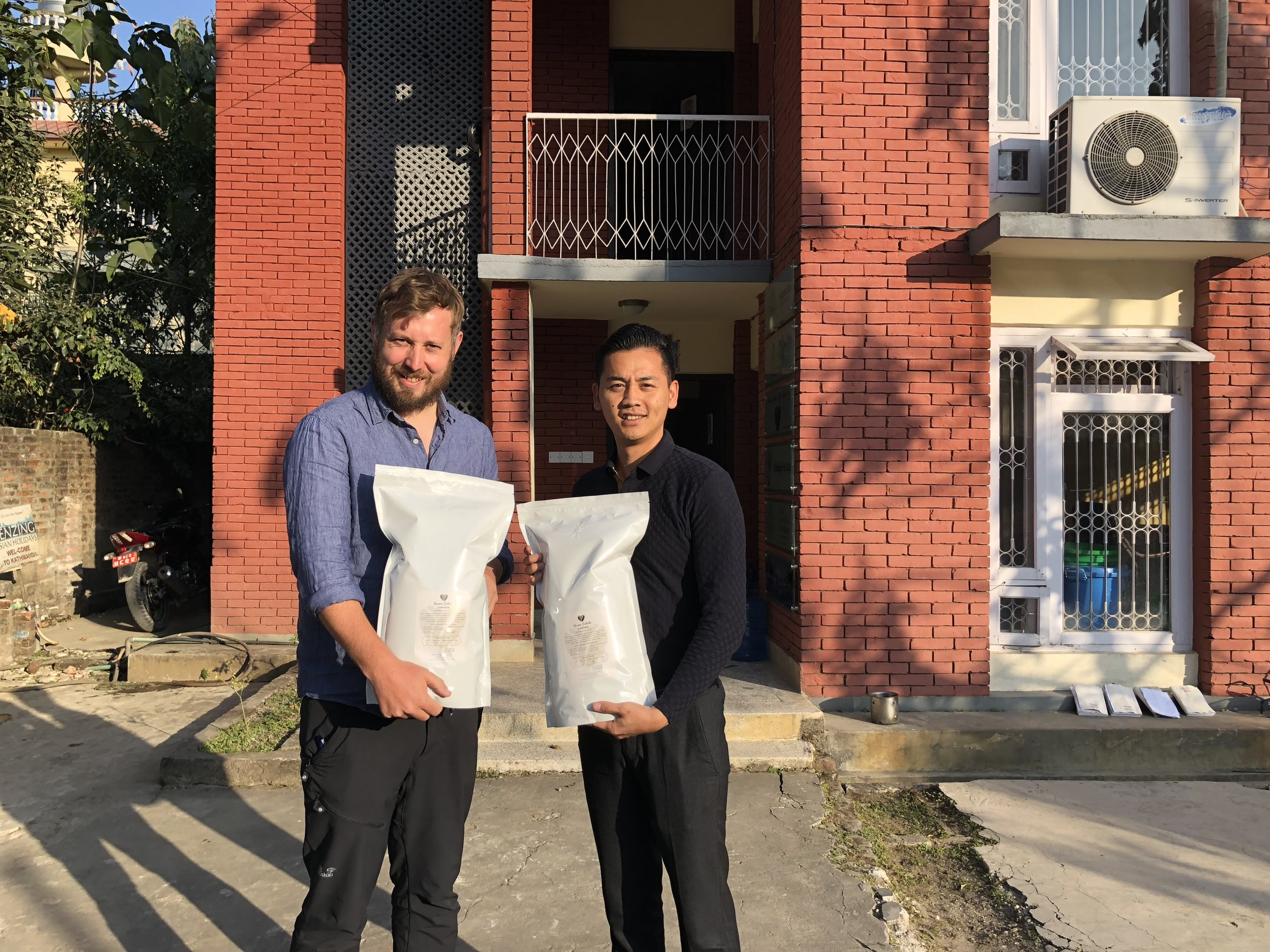 Appa Sherpa, head of Nuwa Coffee Estate, hands over the roasted beans to Dr Morgan Phillips, TGT Co-Director in Kathmandu.