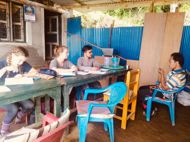 Navin Bhanjade interprets for Charlotte Thomas as they interview local farmer Yubraj Rai about the coffee value chain.