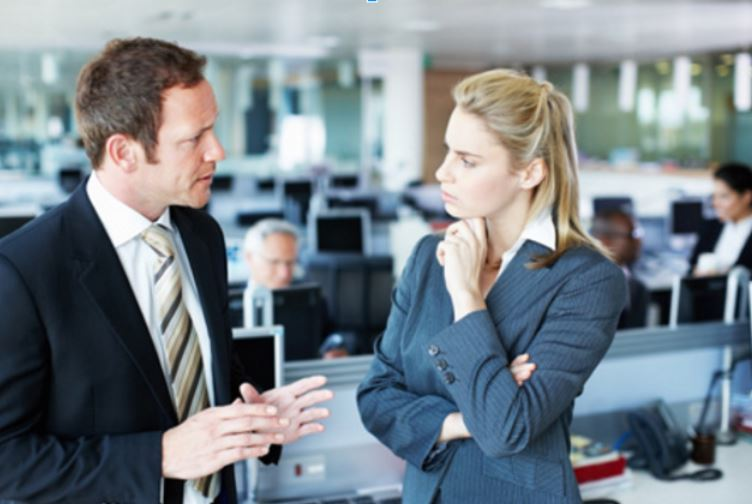 Two people, seemingly having an intense or serious conversation. Woman is displaying closed off body language.