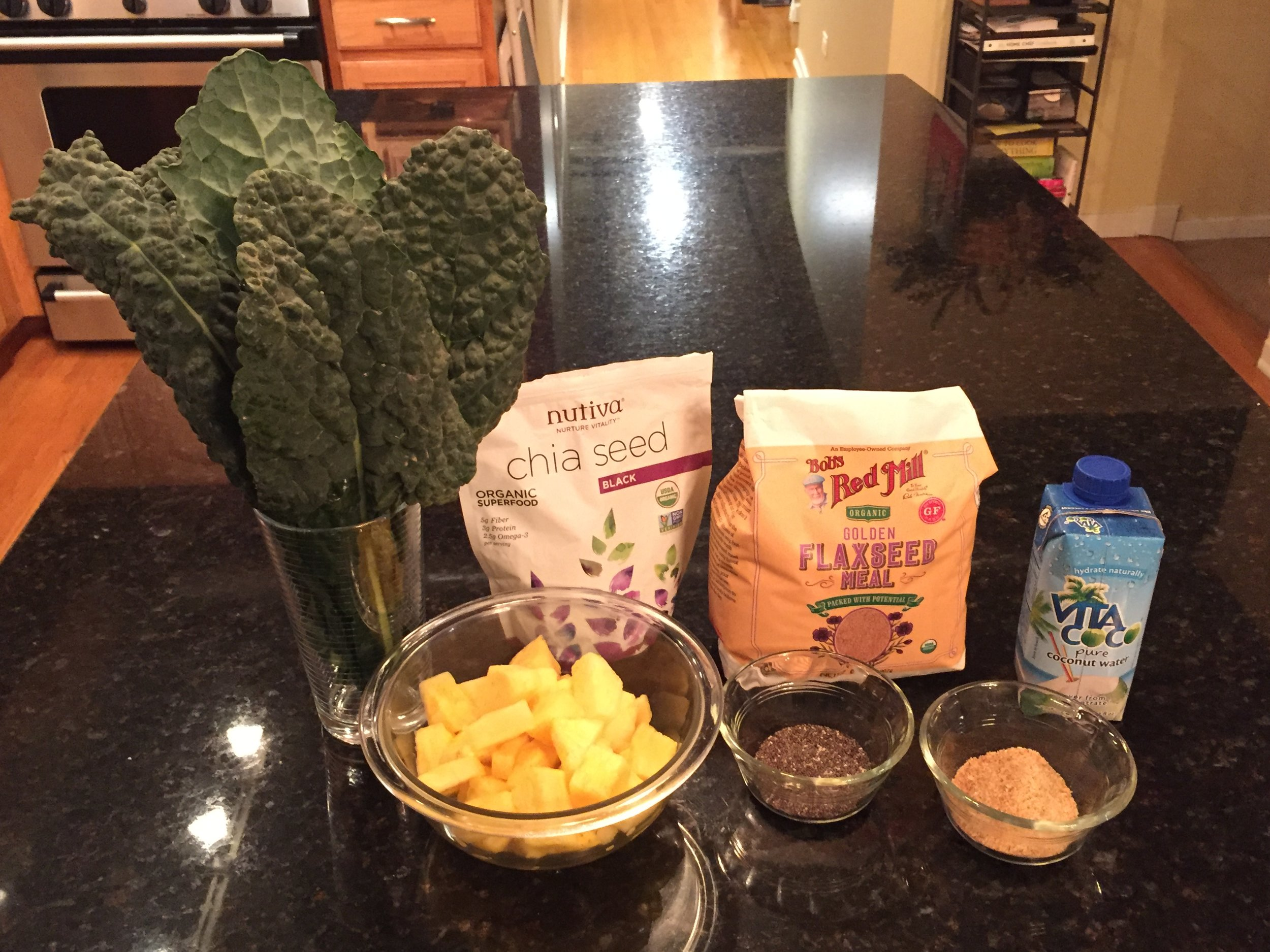 Pictured: Green chard, flax seed meal, coconut water, chopped mango & pineapple, I don't measure anymore. Basically I just fill the blender with fruit & coconut water first, then flax seed, followed by as much greens as I can fit in. Next I cover it all with more regular water. Our finished drink is more like a juice than a smoothie. Chia seeds go into each individual serving last.
