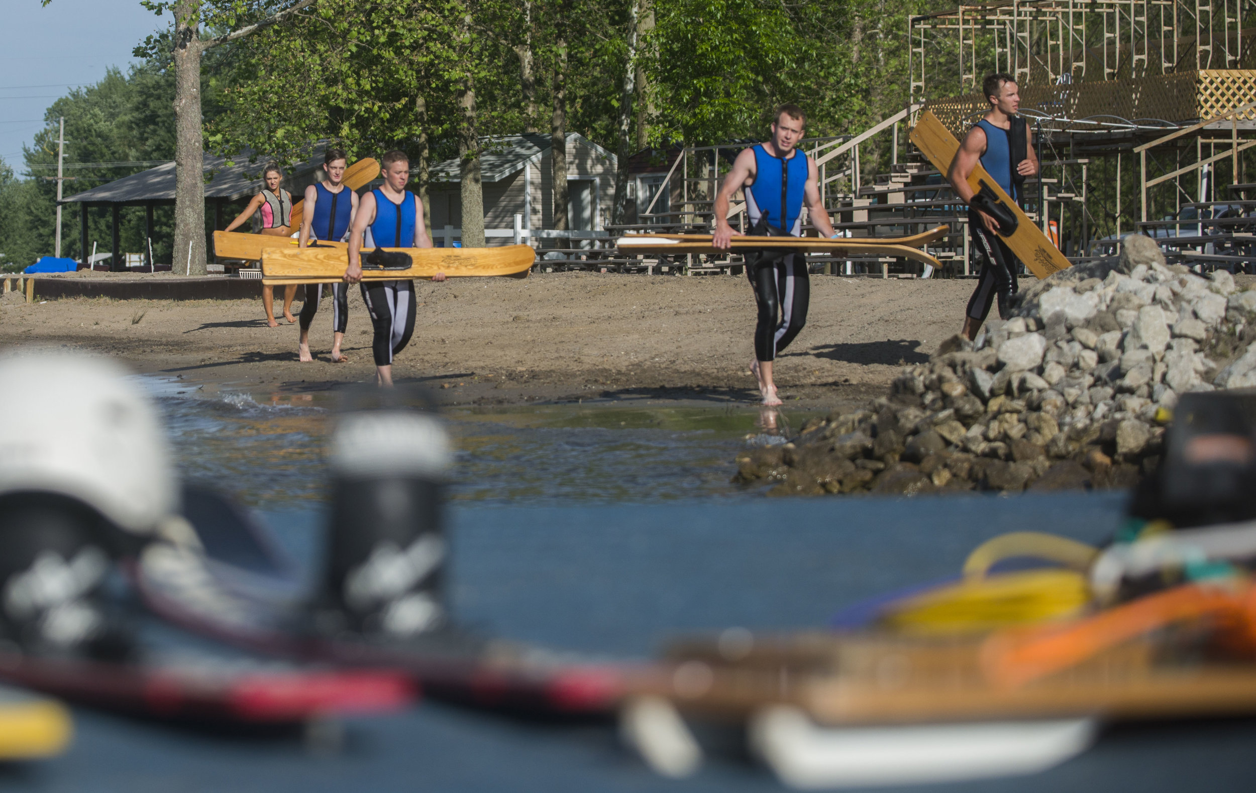 Members of the Lake City Skiers carry their skis from the shore back to the dock after practicing their human pyramid on Hidden Lake. Each show is an hour long, themed-show with two 15-minute intermissions.