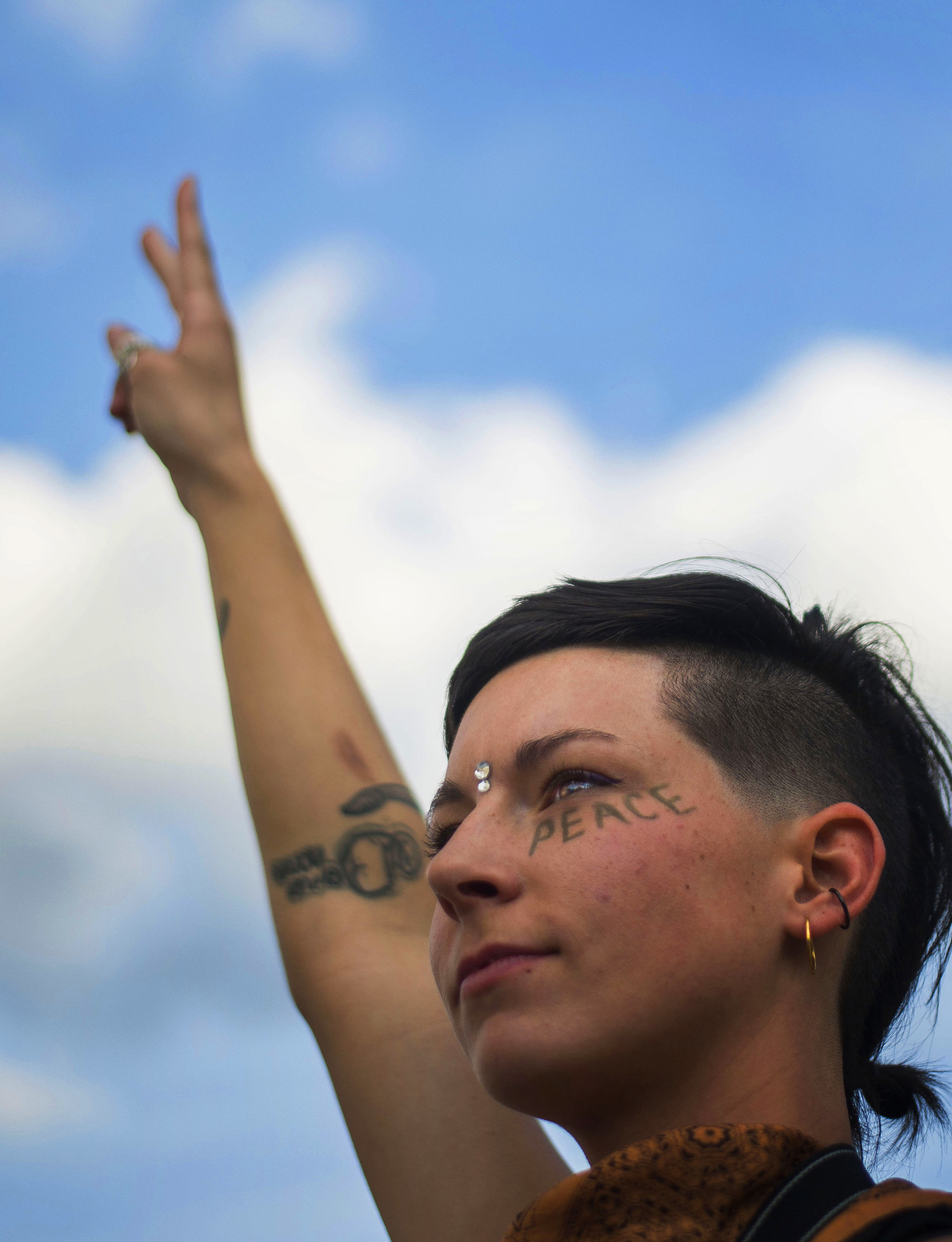 Audrey Conn, 25, stands with a peace sign in the air on the corner of Clinton and Berry streets on June 10, 2016,during the Silent Protest. Many passerbys took photos and videos; those driving honked their horns.